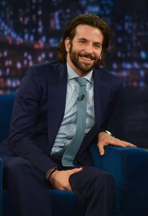 Actor, director y cantante Bradley Cooper con cabello largo y barba, con traje sentado en un sillón