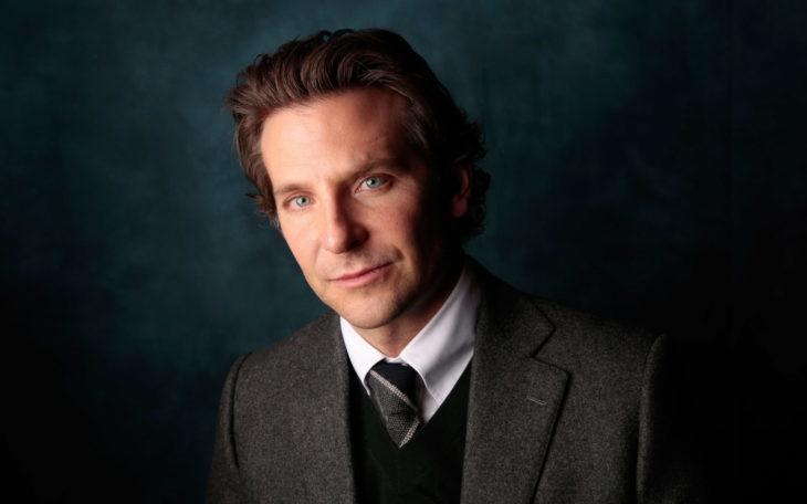 Actor, director y cantante Bradley Cooper sin barba y con traje gris