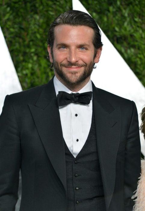 Actor, director y cantante Bradley Cooper con traje negro y moño, con barba y peinado hacia atrás