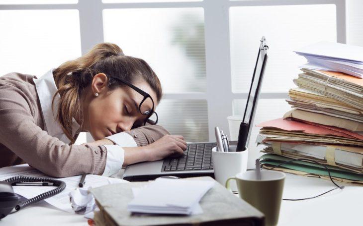 una mujer con lentes está acostada sobre su computadora portátil en una oficina con papeles por todos lados