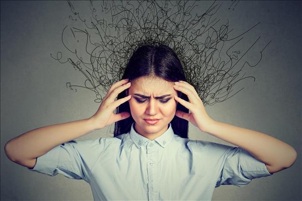 una mujer toca ambos lados de su cabeza con sus manos con una expresión de dolor y salen de ella rayos negros en todas direcciones