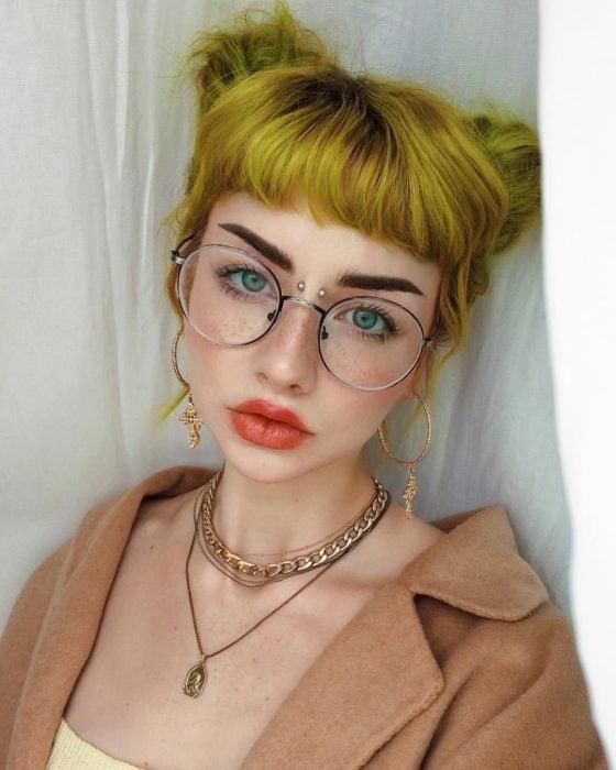 Chica de ojos verdes, pecas, lentes con cabello amarillo peinado con chonguitos y perforación en el puente de la nariz