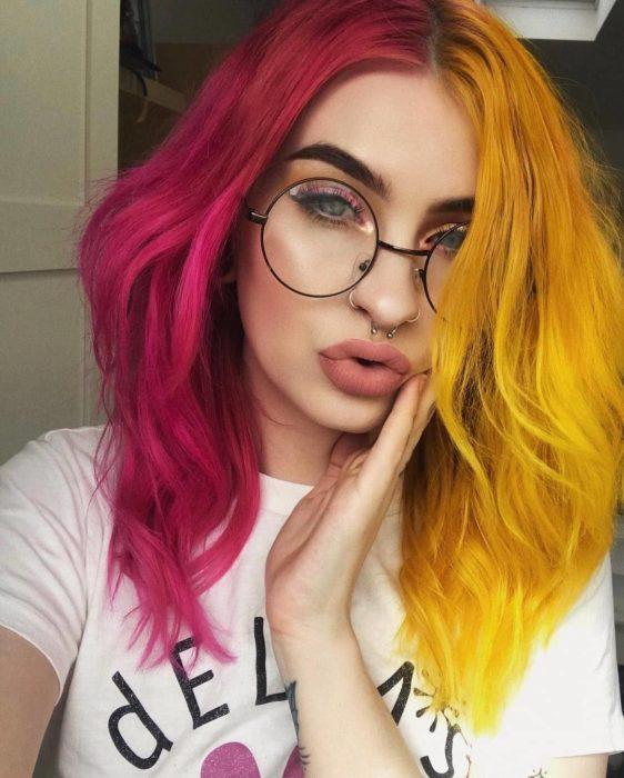 Chica con lentes redondos de aumento, perforaciones en la nariz y tabique, con delineador rosa y cabello teñido de dos colores: rosa magenta y amarillo canario