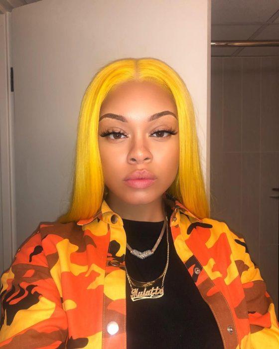 Chica morena sin maquillaje con chamarra de camuflaje anaranjado y cabello amarillo lacio