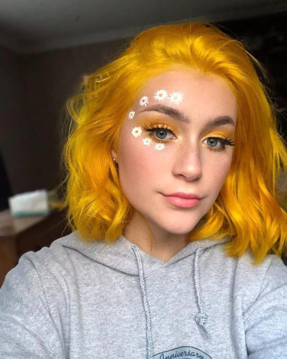Chica de ojos grises con la cara pintada de flores blancas, margaritas; con cabello corte bob hasta los hombros, color amarillo canario