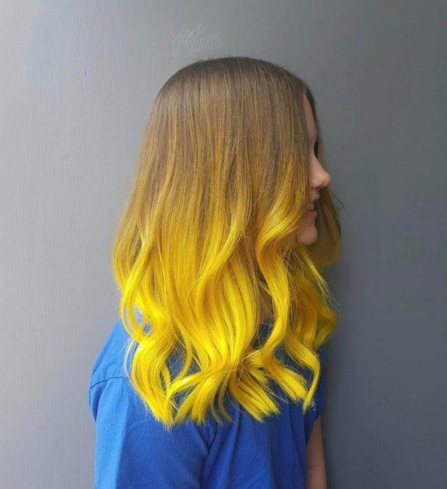Chica de perfil con cabello largo abajo de los hombros de color castaño degradado a amarillo