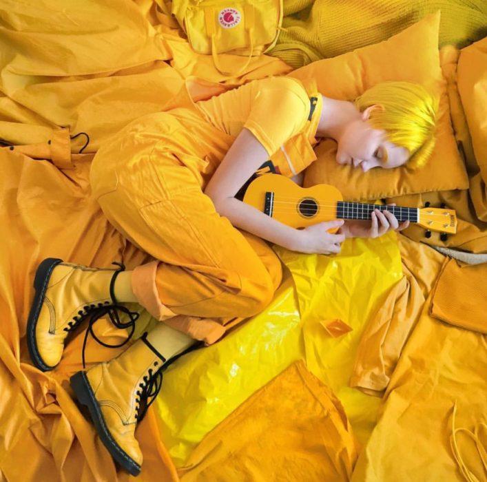 Chica con cabello amarillo y corte pixie, con botas Dr. Martens y ukulele, rodeada de cosas color amarillo