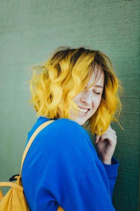 Chica sin maquillaje, sonriendo, con suéter azul y cabello ondulado y color amarillo arriba de los hombros