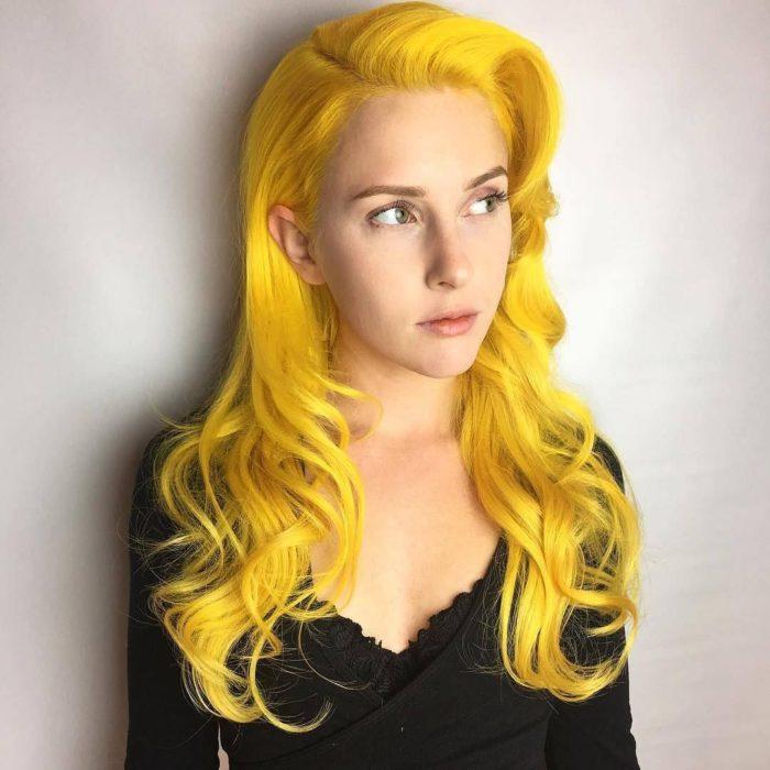 Chica sin maquillaje, de ojos verdes, cabello largo, ondulado teñido de amarillo canario