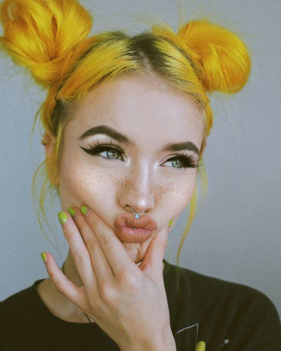 Chica de ojos verdes, pestañas largas, delineado cat eye, pecas, con cabello amarillo peinado en dos chonguitos,
