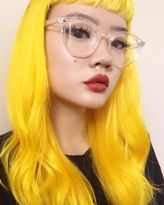 Chica asiática con grandes lentes vintage de aumento, con perforación encima del labio y cabello largo, ondulado y teñido de amarillo brillante