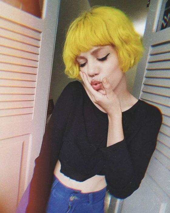 Chica haciendo caras, con corte de hongo y cabello color amarillo patito