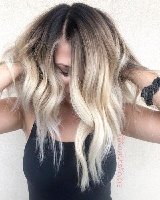 Chica tocando su cabello y cubriendo su rostro con el