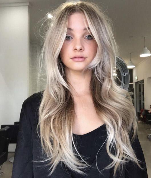 Chica mirando de frente, dentro de una sala, mostrando su larga cabellera rubia coconut