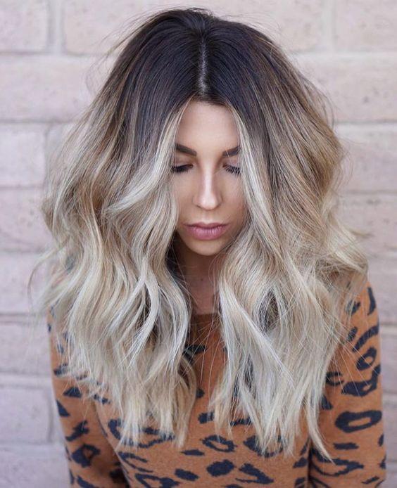 Chica mirando hacia abajo y mostrando su cabello rubio estilo coconut