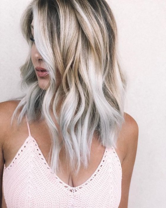 Chica recargada en una pared, girada de perfil, mostrando su cabello largo y rubio