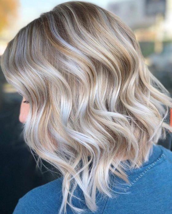 chica de perfil mostrando su cabello corto teñido rubio coconut