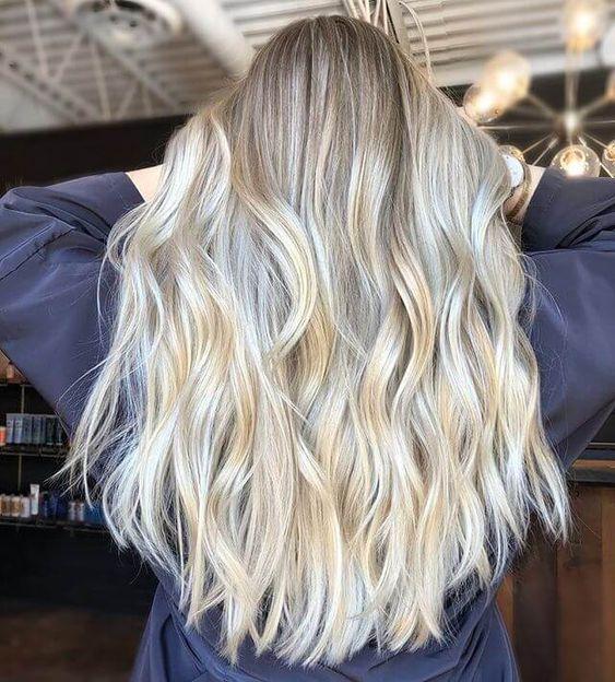 Chica de espaldas tocando su cabeza y mostrando larga cabellera teñida rubio coconut