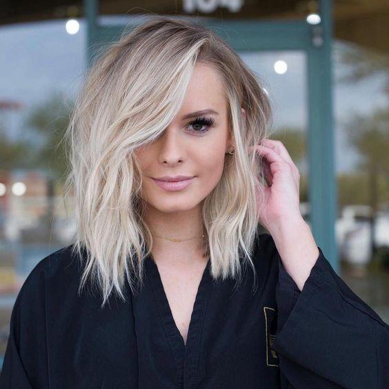 Chica llevando su cabello hacia atrás y sonriendo