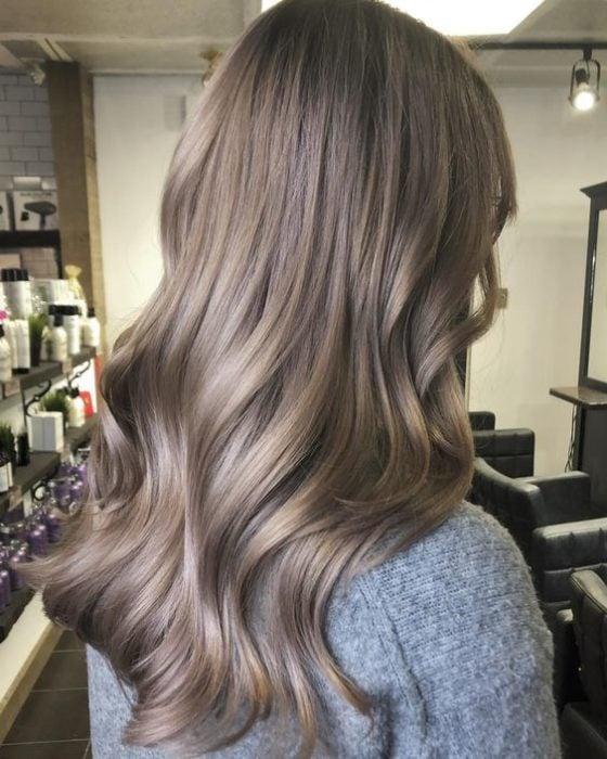 Chica de espaldas mostrando su cabello largo color rubio champiñón