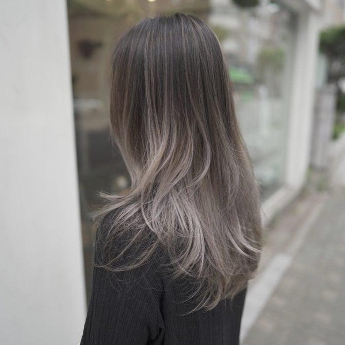 Chica posando de lado, con el rostro cubierto por su cabello color rubio champiñón