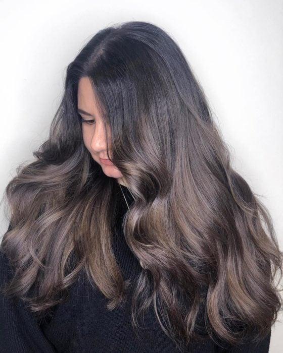 Chica de perfil con cabellera larga y ondulado teñida en color rubio champiñón
