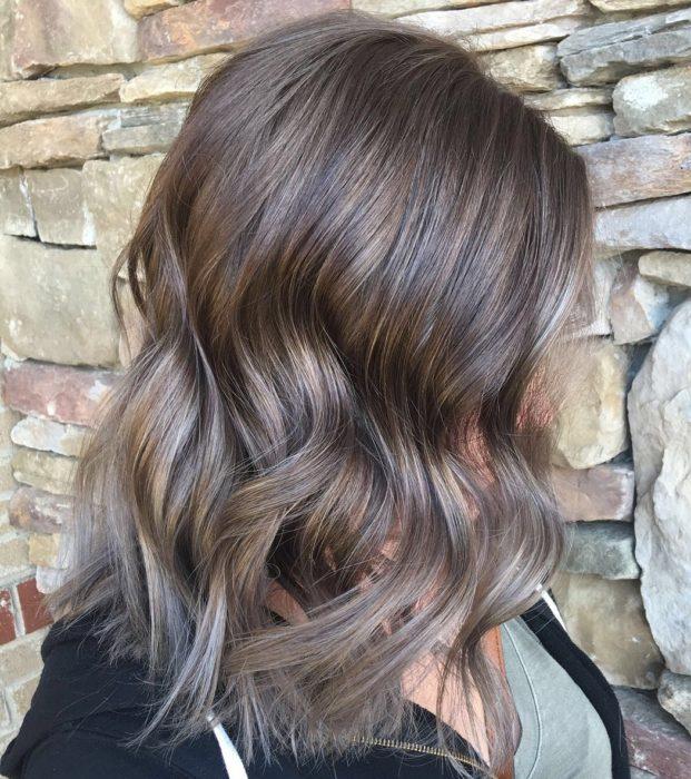 Chica de perfil con la cabeza hacia abajo mostrando su cabello color rubio champiñón