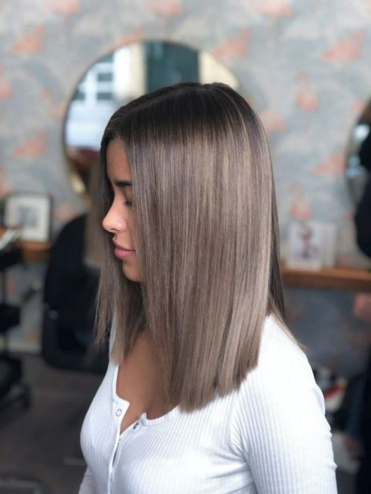 Chica dentro de un salón de belleza, de perfil, mostrando su cabello color rubio champiñón