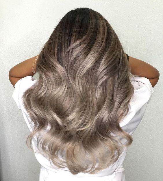 Chica de espaldas jugando con su cabello color rubio champiñón