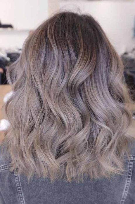 Chica de espaldas mostrando su cabello color rubio champiñón con rizos