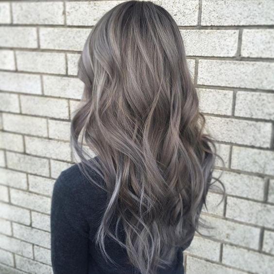 Chisa de espaldas contra una pared de ladrillo gris, mostrando su cabello color rubio champiñón