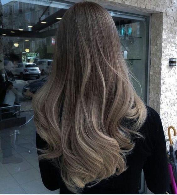 Chica fuera de una estética mostrando su cabello color rubio champiñón