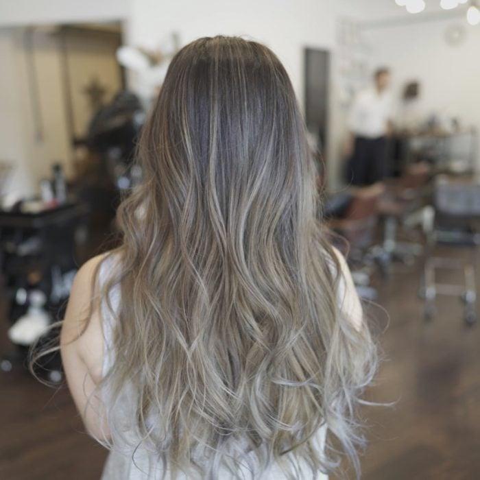Mujer de espaldas mostrando su cabellera larga con cabello color rubio champiñón