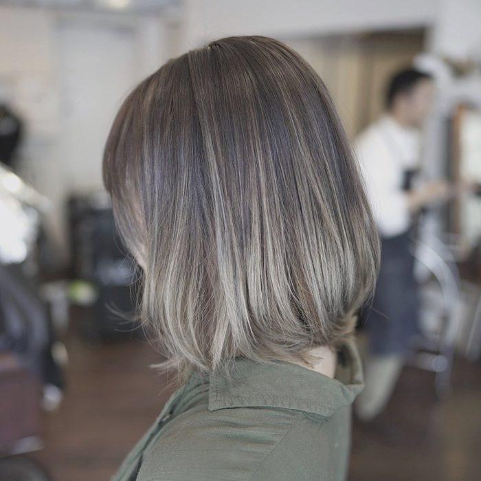 Chica sentada en un sal+on de belleza, de lado, mostrando su cabello color rubio champiñón