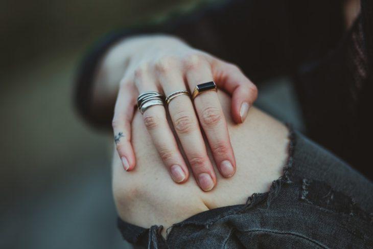 mano de mujer con anillos sobre rodilla