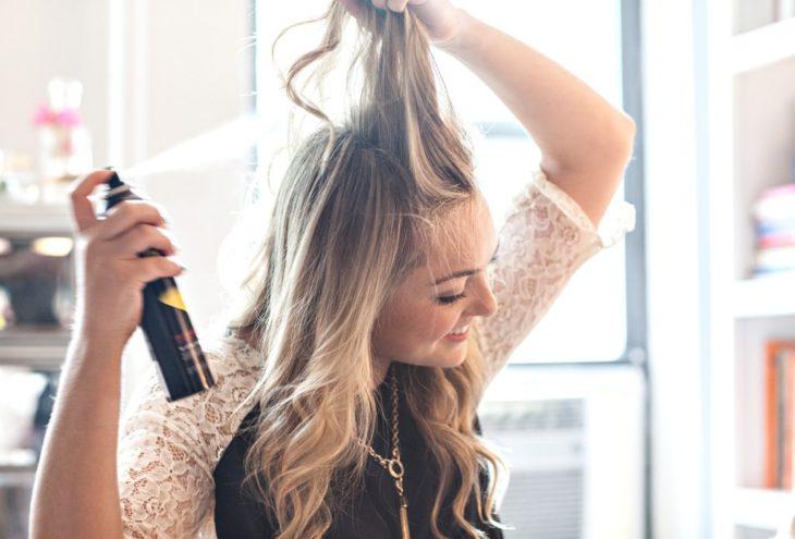 Champú en seco; mujer aplicando spray en el cabello