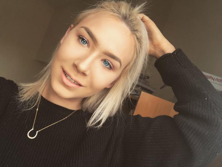Chlo Matthews, chica rubia de ojos azules con suéter negro