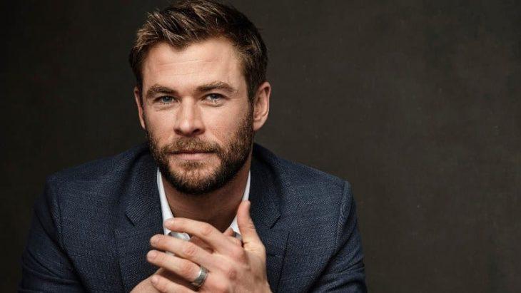 Chris Hemsworth posando para uyna fotografía, usando traje sastre azul marino, mirando al frente y con las palmas de las manos cruzadas