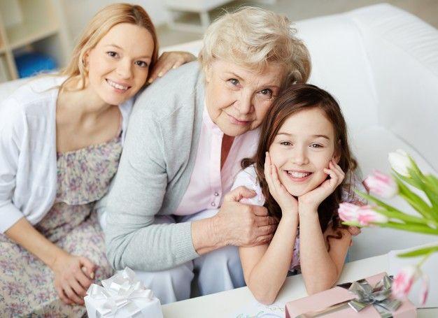 una mamá, abuela y nieta en una sala blanca