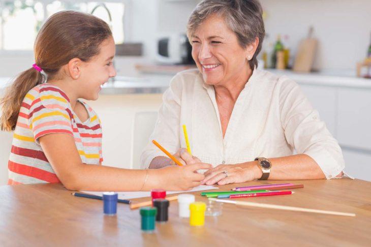 una abuela dibuja con su nieta sobre una mesa de madera dentro de una cocina