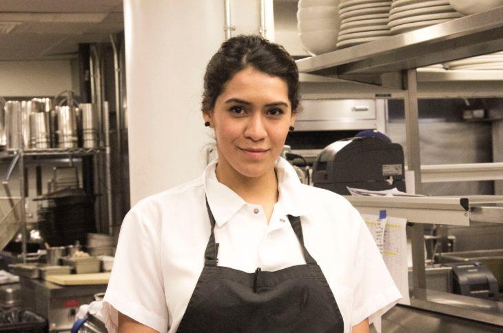 Daniela Soto-Innes en una cocina con blusa blanca y delantal negro pelo recogido