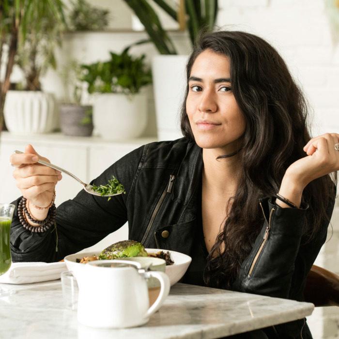 Daniela Soto-Innes comiendo vestida de negro levantando una cuchara con vajilla blanca