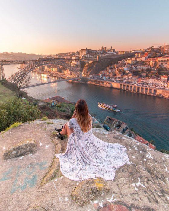 Cosas que debes hacer en vez de enamorarte; chica de vestido largo sentada en una montaña viendo la ciudad y el río