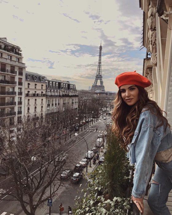 Cosas que debes hacer en vez de enamorarte; chica de cabello castaño con boina roja en un balcón frente a la torre Eiffel