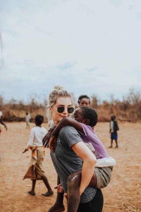 Cosas que debes hacer en vez de enamorarte; chica rubia cargando a un niño moreno en voluntariado