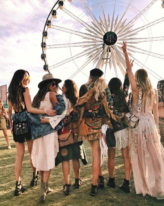 Cosas que debes hacer en vez de enamorarte; grupo de amigas frente a rueda de la fortuna en festival de música