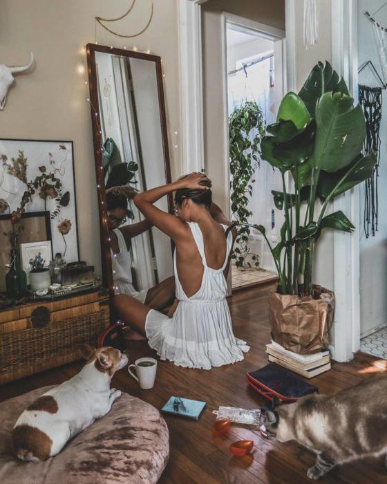Cosas que debes hacer en vez de enamorarte; chica con vestido blanco sentada en el suelo mirándose al espejo con un perro y un gato