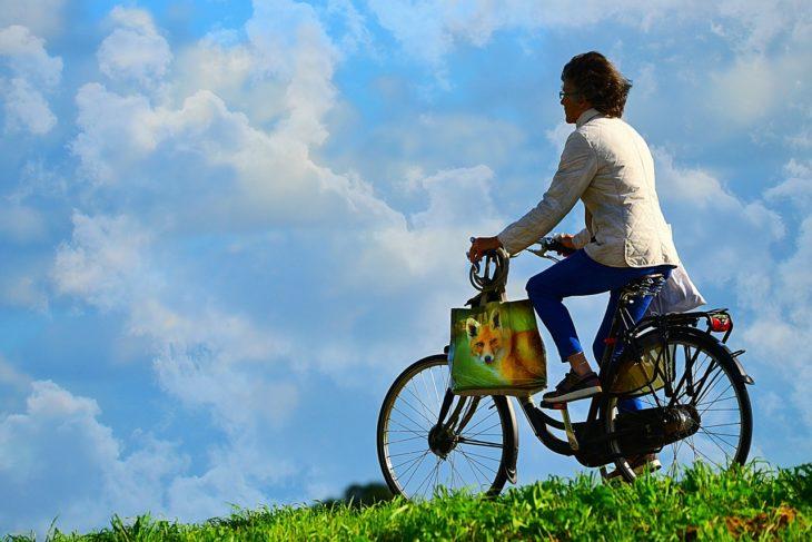 Mujer madura en bicicleta paseando por un prado