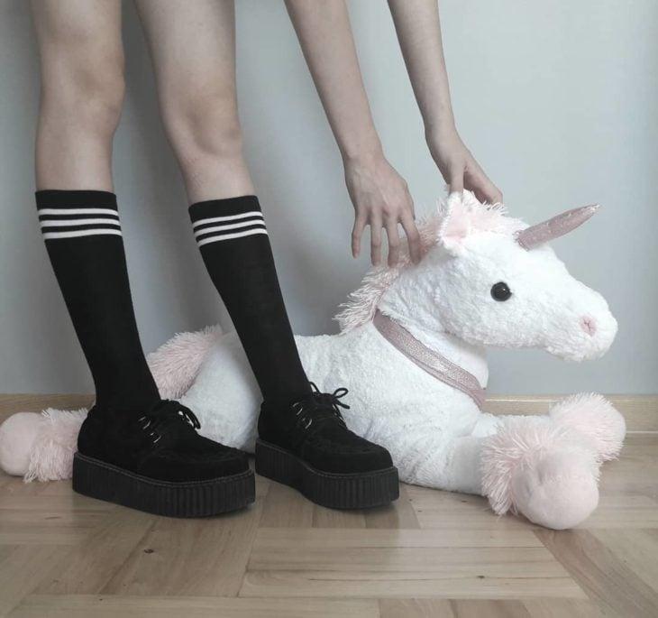 Mujer usando creepers, zapatos con suelas altas y agarrando un peluche de unicornio