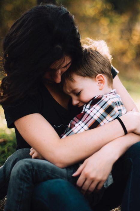 Una mamá sentada abraza en su regazo a su hijo con camisa de cuadros